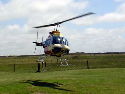 Helicopter just after takeoff, hovering above a green field
