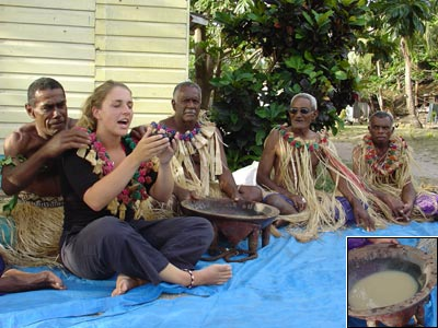 Girl holding kava bowl in front of Fijian men in traditional dress